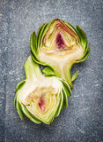 Two halves of the artichoke on gray rustic background Royalty Free Stock Image