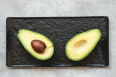 Two halves of avocado on a plate. Two halves of fresh riped avocado on a black serving plate on a gray background. Close up, selective focus royalty free stock photo