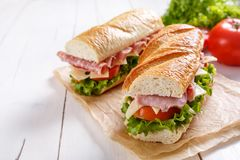 Two Halves of a Baguette Sandwich. Two Halves of a Sub Long Baguette Sandwich with Lettuce, Tomatoes, Cheese and Ham on a Wrapping Papper on a White Table royalty free stock images
