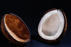 Smoothly cut halves of coconut. Two halves of the coconut are evenly cut lying on a black background Stock Photos