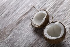 Two halves of coconut on a wooden board royalty free stock image