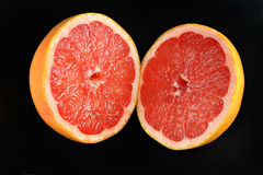 Two halves of cut grapefruit lying on black. Background royalty free stock photos