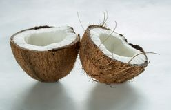 Two halves of coconut are on the table. Two halves of two halves of fresh coconut are on the table coconut are on the table royalty free stock image