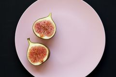 Two halves of fresh fig on pink plate over black background, top view. Flat lay. Overhead royalty free stock photos