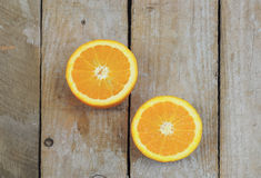 Two halves of fresh orange. Fresh orange cut in half on wooden table Royalty Free Stock Image