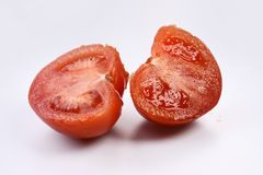 Two halves of fresh red rustic tomato on a white background. Stock Photography