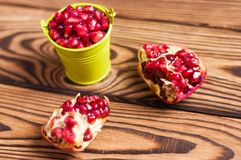 Two halves of fresh ripe red pomegranate with seeds near full green metal bucket of seeds. On old brown weathered rustic wooden table royalty free stock image