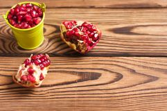 Two halves of fresh ripe red pomegranate with seeds near full green metal bucket of seeds. On old brown weathered rustic wooden table stock photos