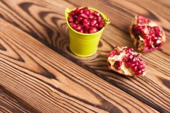Two halves of fresh ripe red pomegranate with seeds near full green metal bucket of seeds. On old brown weathered rustic wooden table royalty free stock photo