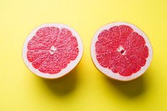 The two halves of the grapefruit cut lengthwise on a yellow background.  stock images