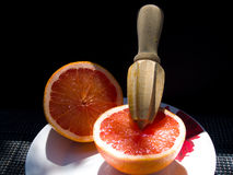 Two Halves of Grapefruit. Two halves of a grapefruit on a white plate with a wooden instrument. Black backgroung Stock Photo