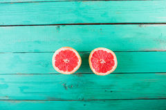 Two halves of grapefruit on a wooden turquoise background. Copyspace stock photography