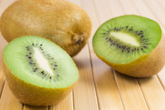 Two halves of green kiwi fruit on table Royalty Free Stock Image