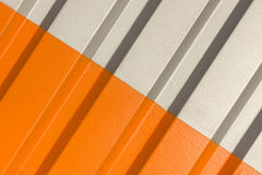 The two halves grey and orange of the figure of corrugated texture. Concept: reliable, abstract, creative, art, fence royalty free stock photos