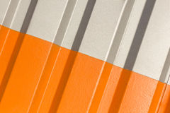 The two halves grey and orange of the figure of corrugated texture. Concept: reliable, abstract, creative, art, fence stock photo