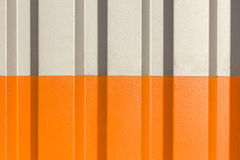 The two halves grey and orange of the figure of corrugated texture. Concept: reliable, abstract, creative, art, fence royalty free stock photo
