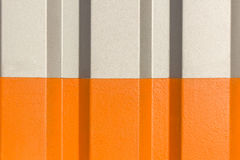 The two halves grey and orange of the figure of corrugated texture. Concept: reliable, abstract, creative, art, fence stock image