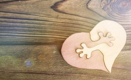 Two halves of the heart are connected on a wooden background. Valentine`s Day. love obyatya royalty free stock image