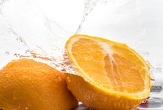 Two halves of juicy orange close up with a splash of water on them and flying water above.  royalty free stock photo