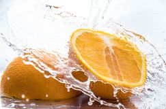 Two halves of juicy orange close up with a splash of water on them and flying water above.  stock photos