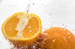 Two halves of juicy orange close up with a splash of water on them and flying water above.  stock photography