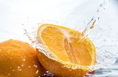 Two halves of juicy orange close up with a splash of water on them and flying water above.  stock images