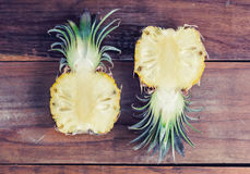 Two halves of juicy pineapple on old wooden table Royalty Free Stock Photos
