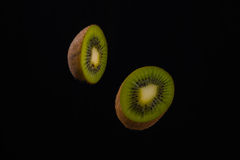 Two halves of kiwi and on black background. Two halves of kiwi and on black background Stock Photo