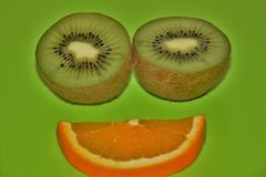 Two halves of kiwi and a slice of orange. On a green background Royalty Free Stock Image