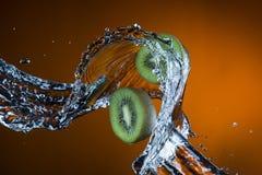 Two halves of kiwi and splash of water on orange background.  stock image