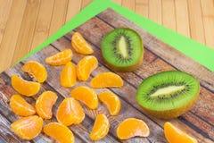 Two halves of kiwi and tangerine. Slices royalty free stock photo