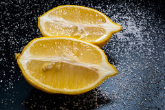 Two halves lemon on a black table with sugar. Two halves lemon on a black table Royalty Free Stock Image