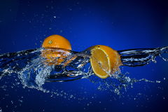 Two halves of lemon and splash of water on blue background.  Stock Photo