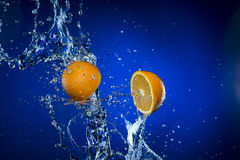 Two halves of lemon and splash of water on blue background. Two halves of lemon and splash of water on blue background Royalty Free Stock Photos