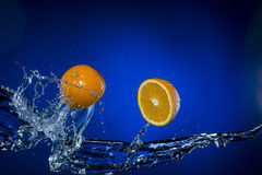 Two halves of lemon and splash of water on blue background. Two halves of lemon and splash of water on blue background Stock Photo