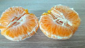 Two halves of mandarin. Two peeled mandarin halves on a wooden background royalty free stock photography