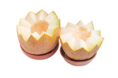 Two halves of melon in ceramic bowls on a light background royalty free stock photography