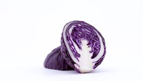 Two halves of mini purple cabbage. Cross cut. Rotating on the turntable isolated on the white background. Close-up. Macro stock video
