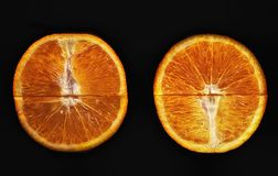 Two halves of an orange. On a black background stock image