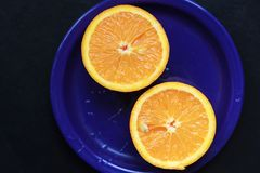 The two halves of orange on a blue plate. Ready for juicing. Top view stock photography