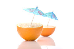Two halves of an orange with cocktail umbrellas. On a white background stock photos