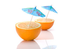 Two halves of an orange with cocktail umbrellas. On a white background stock photo