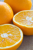 Two halves of an orange and two whole oranges close-up. Two halves of an orange and two whole oranges closeup stock photo