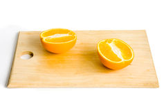 Two halves of orange on wooden plate. Photo of isolated on white still life of two orange halves on wooden plate royalty free stock photos