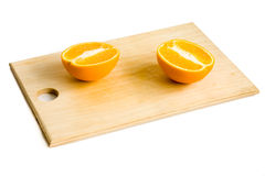 Two halves of orange on wooden plate Stock Images
