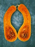 Two halves of a pear-shaped pumpkin of orange color, are located on a background of turquoise color vertically royalty free stock photography