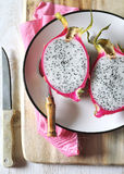 Two halves of pitahaya. On wooden cutting board stock image