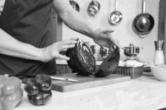 Two halves of red cabbage on kitchen board. Close up of two nonproportional halves of fresh red cabbage being kept by mans hands on wooden board against kitchen royalty free stock image