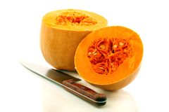 Two halves of a ripe pumpkin and a table knife. Stock Photography