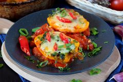 Two halves of stuffed bell peppers. On a dark plate royalty free stock photography